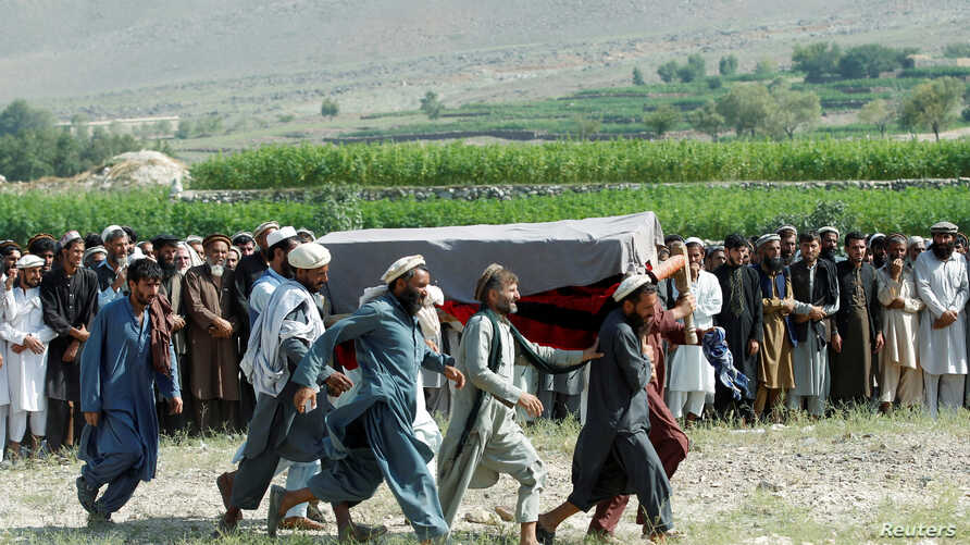 Men carry a coffin of one of the victims after a drone strike, in Khogyani district of Nangarhar province, Afghanistan…