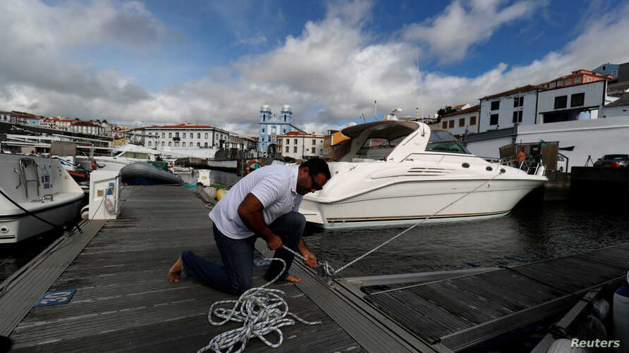 A man reinforces with ropes the mooring of his boat at a port before the arrival of Hurricane Lorenzo in Angra do Heroismo in the Azores islands, Portugal, Oct. 1, 2019.