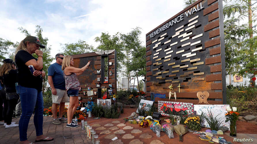 FILE - People look at a Remembrance Wall at the Las Vegas Healing Garden during the one-year anniversary of the mass shooting in Las Vegas, Nevada, Oct. 1, 2018.