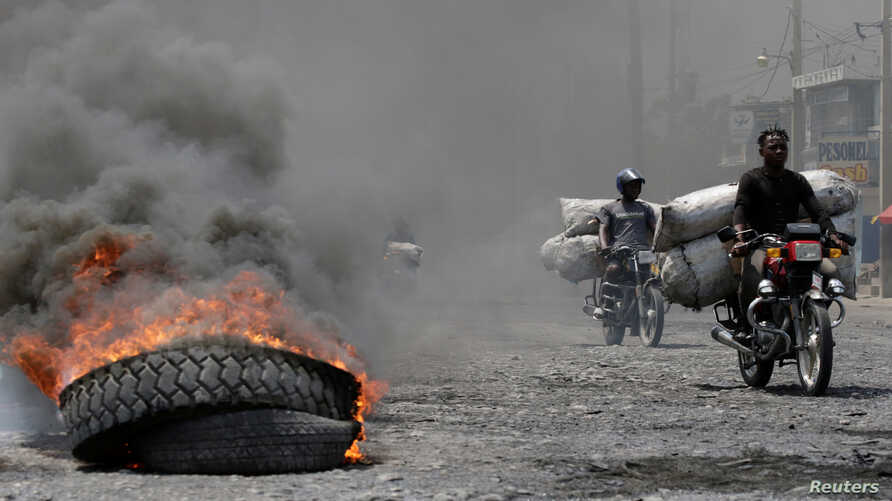 Men riding motorbikes pass next to a burning tire at a barricade in a street of Port-au-Prince, Haiti, Oct. 2, 2019.