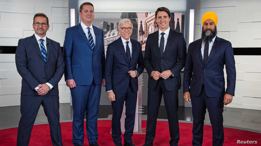 Bloc Quebecois leader Yves-François Blanchet, Conservative leader Andrew Scheer, TVA network host Pierre Bruneau, Liberal leader and Prime Minister Justin Trudeau and NDP leader Jagmeet Singh pose before a debate in Montreal, Quebec, Canada, Oct. 2, 2019.