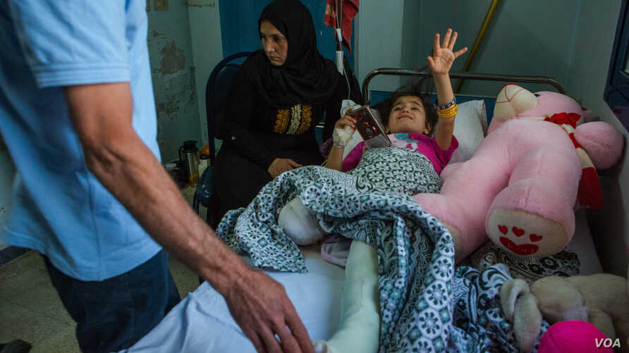 Sara, 8, cries as her father looks at her one broken leg — the other has been severed — in Qamishli, Syria, Oct. 15, 2019. (Y. Boechat/VOA)