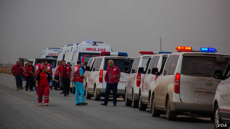 A convoy prepares to take at least 35 injured people from the war zone, Oct. 19, 2019. Five patients died before they were rescued on the outskirts of Ras al-Ayn, Syria. (Yan Boechat/VOA)