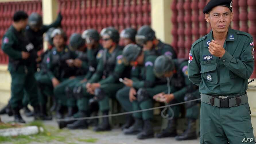 FILE - Cambodian police officers are posted outside a building in Phnom Penh, Aug. 22, 2018.