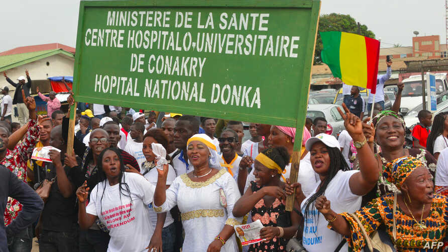 """Demonstrators hold a sign reading """"Health ministery, Conakry's University Hospital (CHU), Donka's national hospital"""" as supporters of Guinea's President Alpha Conde take part in a rally in support of the President in Conakry on October 31, 2019."""