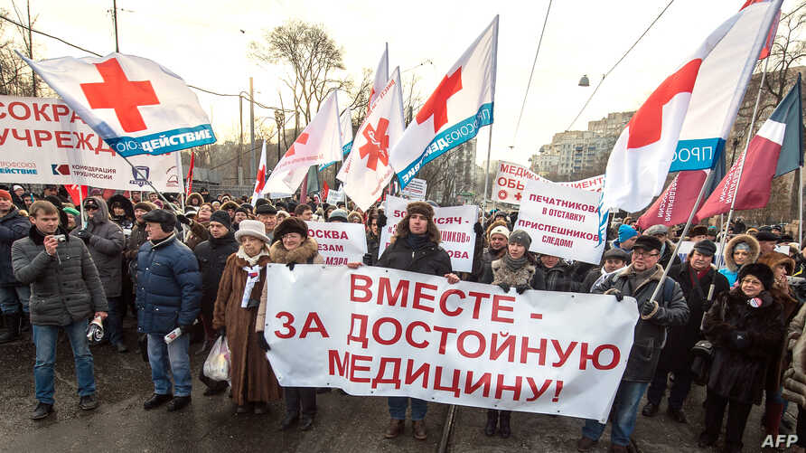 """FILE - Protesters carry a banner reading """"Together for decent medical care!"""" as they march in a street in Moscow, Russia, Nov. 30, 2014."""