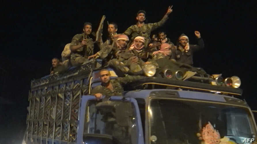 In this image grab from AFP footage, a convoy of Syrian regime troops arrives in the northern border town of Kobane (also known in Arabic as Ain Arab), Oct. 24, 2019.