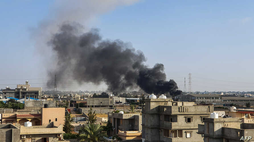 FILE - A smoke plume rises in Tajoura, south of the Libyan capital Tripoli, June 29, 2019, following a reported airstrike.