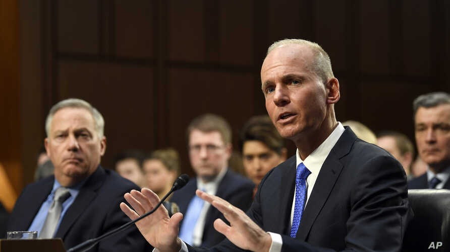 Boeing Company President and Chief Executive Officer Dennis Muilenburg, right, sitting next to Boeing Commercial Airplanes Vice President and Chief Engineer John Hamilton, left, testifies on Capitol Hill in Washington, Oct. 29, 2019.