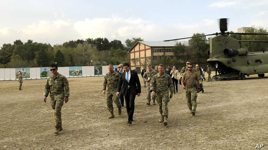 U.S. Defense Secretary Mark Esper, center, walks Gen. Scott Miller, right, chief of the U.S.-led coalition in Afghanistan, at the U.S. military headquarters in Kabul, Oct. 20, 2019.