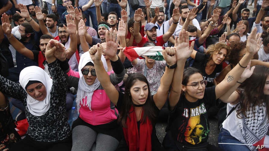 Anti-government protesters shout slogans as they block a main highway, in Beirut, Lebanon, Saturday, Oct. 26, 2019.