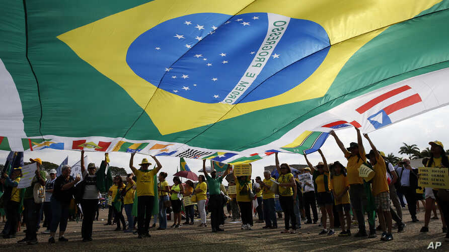 FILE - Demonstrators hold a Brazilian flag during an act in support of operation Car Wash and former judge Sergio Moro, in front of Supreme Court headquarters in Brasilia, Brazil, Sept. 25, 2019.