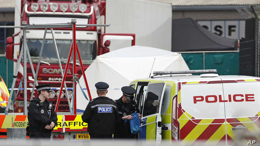 Police officers are on the scene after a truck, in rear, was found to contain a 39 dead bodies, later found to be Chinese nationals, in Thurrock, England, Oct. 23, 2019.