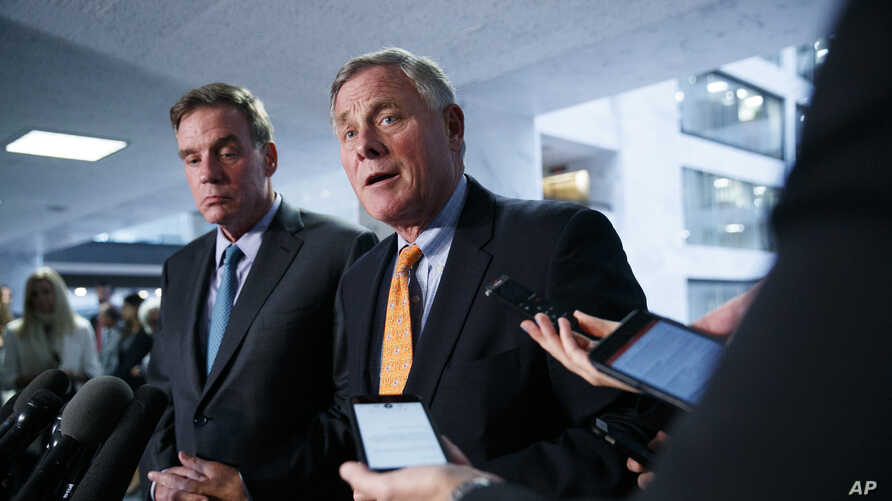 FILE - Republican Senator Richard Burr, right, chairman of the Senate Intelligence Committee, and Democratic Senator Mark Warner, committee vice chair, speak to the media on Capitol Hill in Washington, Sept. 26, 2019.
