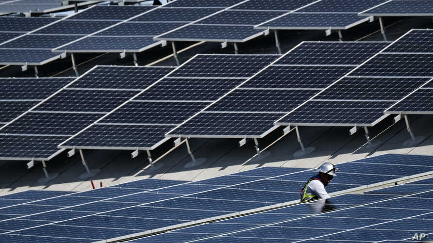 FILE - A worker installs solar panels on a roof at Van Nuys Airport in Los Angeles, California, Aug. 8, 2019.