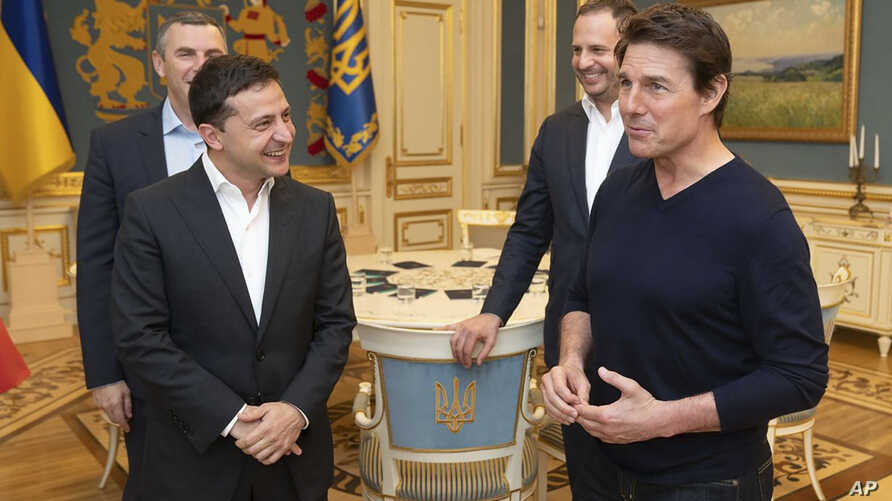 Ukrainian President Volodymyr Zelenskiy, left, and American actor, film director and producer Tom Cruise talk during their meeting in Kyiv, Ukraine, Sept. 30, 2019.