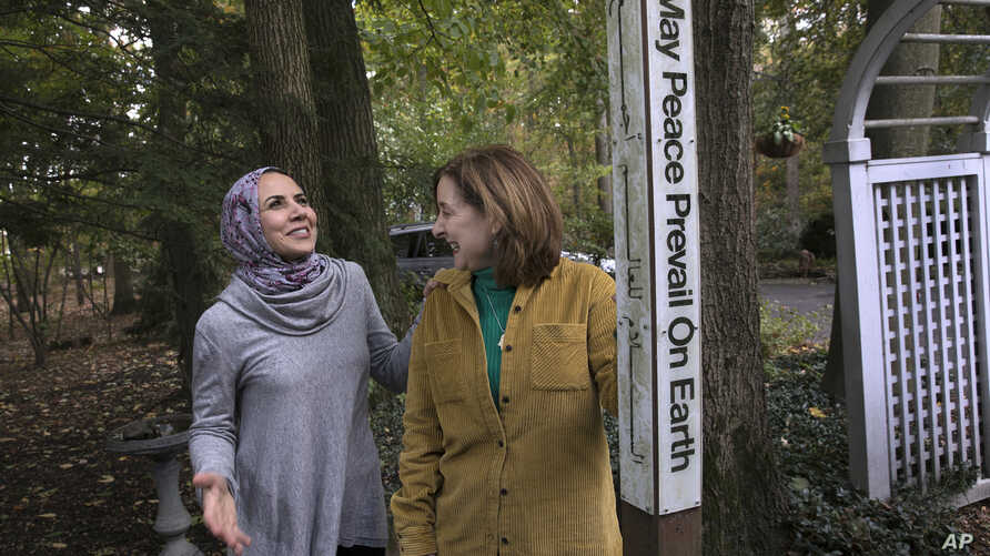 Heba Macksoud, left, of Princeton, New Jersey, and Sheryl Olitzky, members of the Sisterhood of Salaam Shalom, stand near a Peace Pole, with English and Arabic writings, in North Brunswick, New Jersey, Oct. 17, 2019.