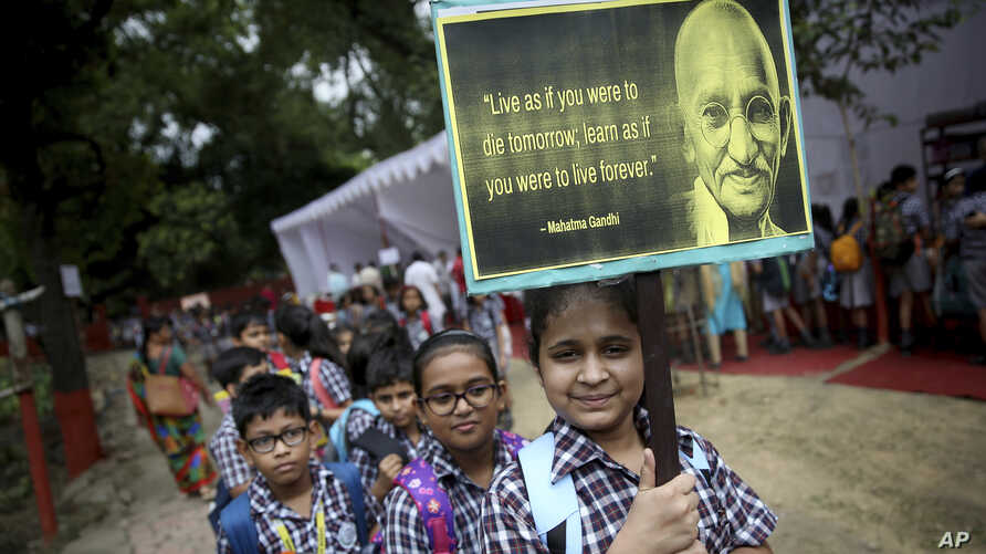 A schoolgirl holds a placard as students participate in an event to celebrate the 150th birth anniversary of India's independence leader Mahatma Gandhi in New Delhi, India, Oct. 1, 2019.