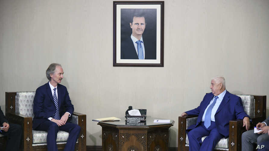 FILE - In this photo released by the Syrian official news agency SANA, the U.N.'s special envoy for Syria Geir Pedersen, left, meets with Syrian Foreign Minister Walid al-Moallem, in Damascus, Syria, Sept. 23, 2019.