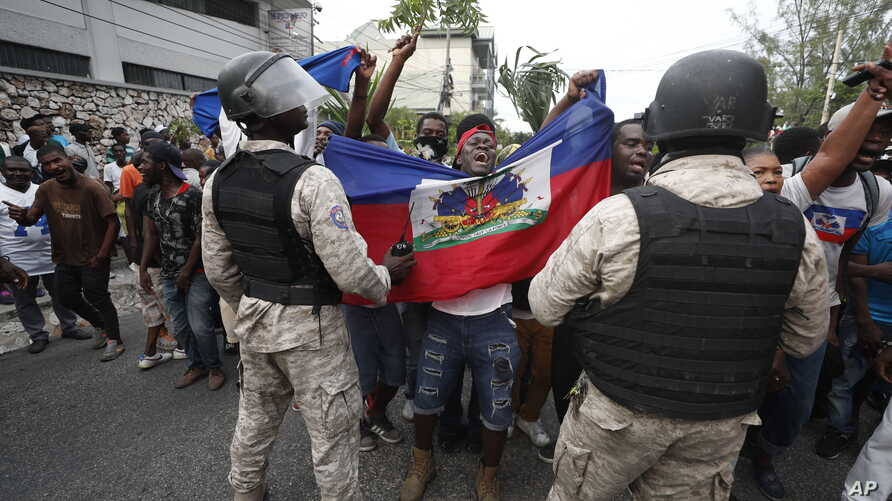 FILE - Anti-government protesters holding a Haitian flag confront security forces during a march in Port-au-Prince, Haiti, Oct. 20, 2019.