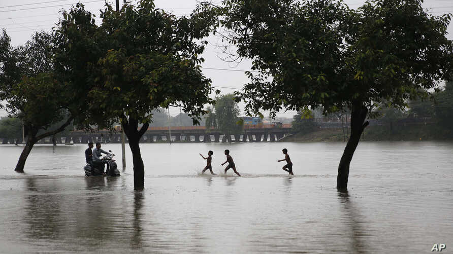 Boys play in the rain on a flooded street in Prayagraj, in the northern Indian state of Uttar Pradesh, Sept. 28, 2019.