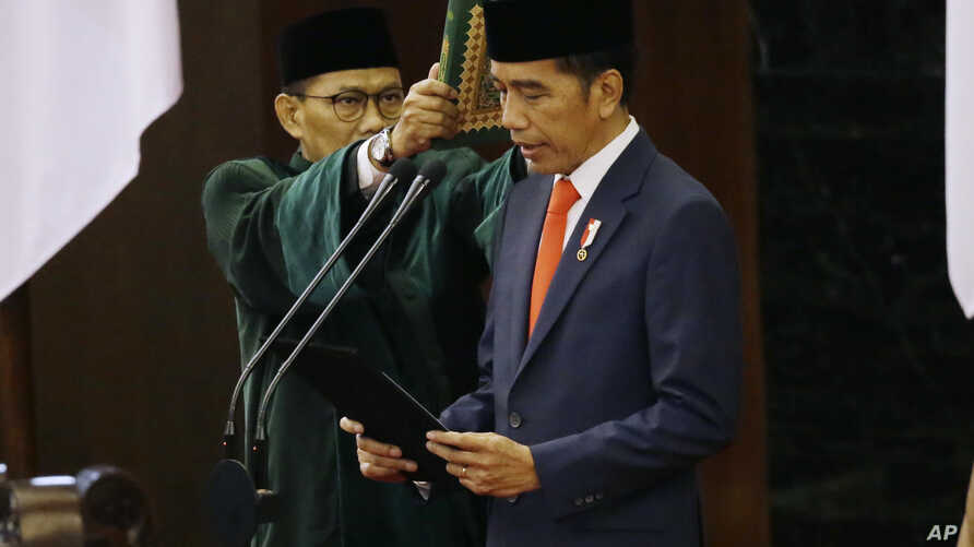 Indonesian President JokIndonesian President Joko Widodo, right, reads his oath during his inauguration ceremony at the parliament building in Jakarta, Oct. 20, 2019.  Widodo, right, reads his oath during his inauguration ceremony as the country's seventh president at…