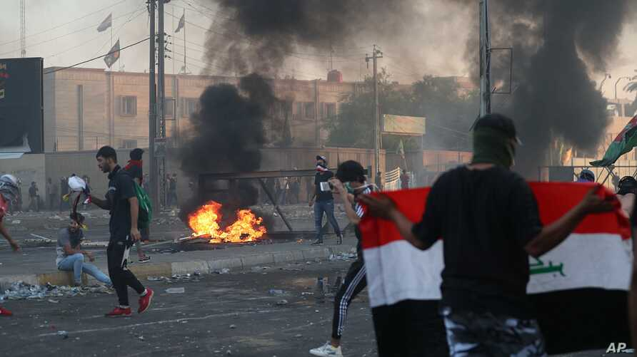 Anti-government protesters set fires and block a street during a violent rally in Baghdad, Iraq, Oct. 3, 2019.