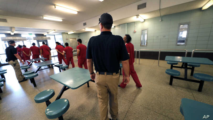 Detainees leave the cafeteria under the watch of guards during a media tour at the Winn Correctional Center in Winnfield, La., Sept. 26, 2019.