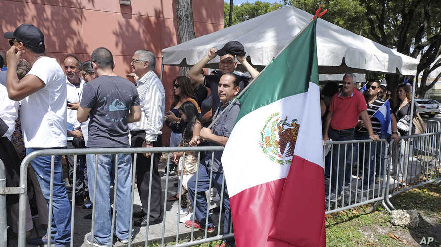 A fan holds a Mexican flag while he waits in line outside of the Miami-Dade County Auditorium during a public funeral for the late Mexican singer Jose Jose, Oct. 6, 2019, in Miami.