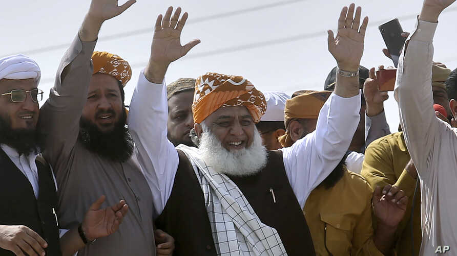 Maulana Fazlur Rehman, center, head of the Jamiat Ulema-e-Islam party, waves to supporters on his arrival to lead an anti-government march, in Karachi, Pakistan, Oct. 27, 2019.
