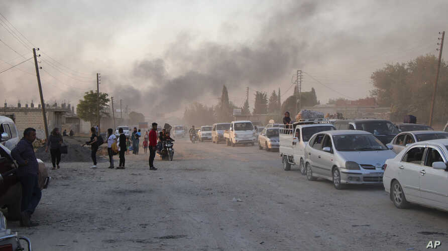 People flee shelling by Turkish forces in Ras al-Ayn, northeast Syria, Oct. 9, 2019.