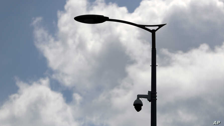 FILE - A high-tech video camera hangs from a lamppost in Belgrade, Serbia, July 17, 2019.