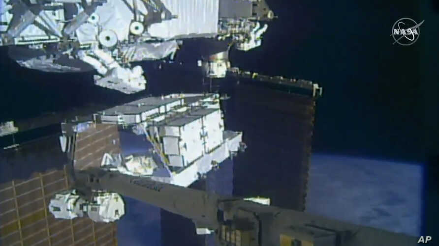 In this image made from video provided by NASA, NASA astronauts Christina Koch and Andrew Morgan work outside the International Space Station, Oct. 6 2019.