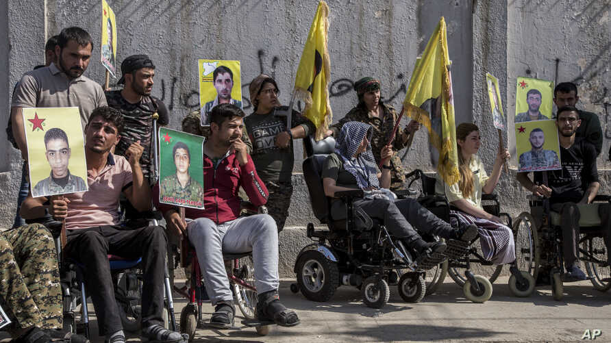Wounded Kurdish fighters hold portraits of comrades who were killed fighting against IS militants, during a demonstration outside the U.N. building in Qamishli, northeast Syria, against an anticipated Turkish incursion, Oct. 8, 2019.