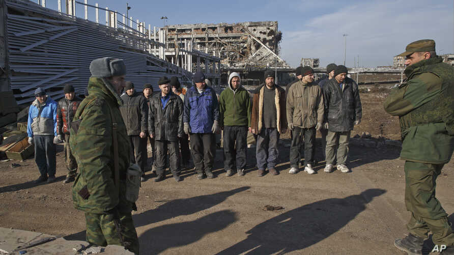 FILE - Ukrainian prisoners of war stand as Russia-backed separatists watch in front of the destoryed airport building outside Donetsk, Ukraine, Feb. 25, 2015.
