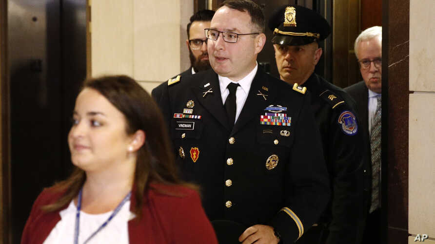 Army Lieutenant Colonel Alexander Vindman, a military officer at the National Security Council, center, arrives on Capitol Hill in Washington, Oct. 29, 2019, to be interviewed as part of the impeachment inquiry into President Donald Trump.