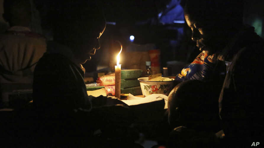 FILE - With electricity unavailable or unaffordable for many, Learnmore Mavhura, right, helps his 9-year old nephew, Lionel, do his homework by candlelight, in Harare, Zimbabwe, July 23, 2019.