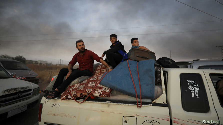 A man and two boys sit on belongings at the back of a truck as they flee Ras al-Ayn, Syria, Oct. 9, 2019, with smoke billowing in the background during a Turkish offensive.