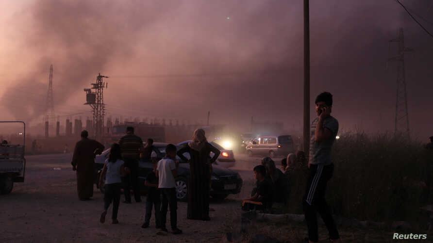 People stand together as they flee Ras al Ain town, Syria, Oct. 9, 2019, during an offensive by Turkish troops.
