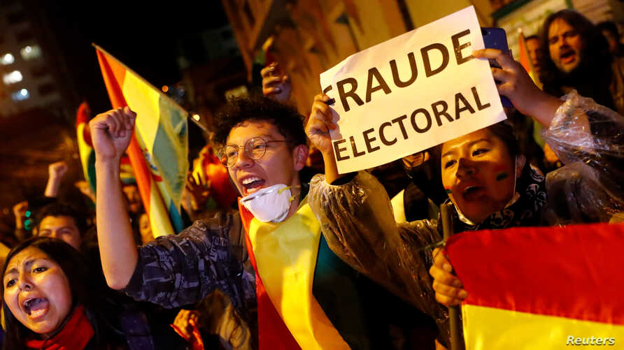 """A protestor holds a banner reading """"Electoral Fraud"""" as she takes part in a march in La Paz, Bolivia, Oct. 25, 2019."""