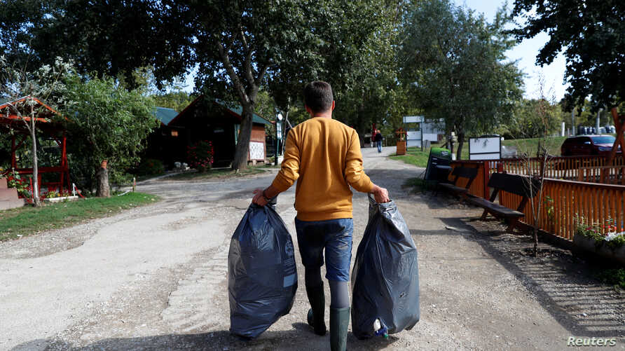 Bence Pardy, 32, carries plastic bags full of waste in Tiszafured, Hungary, Oct. 1, 2019.