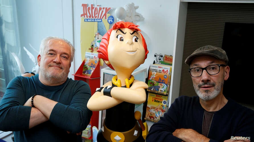 "Author Jean-Yves Ferri and illustrator Didier Conrad pose with a figure of the character Adrenaline during an interview about their new Asterix comic book ""La Fille De Vercingetorix"" in Vanves near Paris, Oct. 22, 2019."