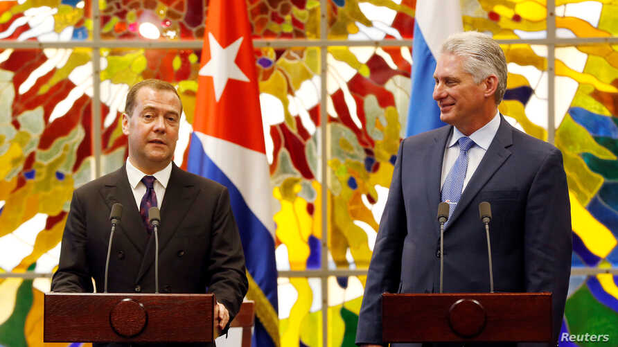 Cuba's President Miguel Diaz-Canel watches Russia's Prime Minister Dmitry Medvedev as he speaks at the Revolution Palace in Havana, Cuba, Oct. 3, 2019.