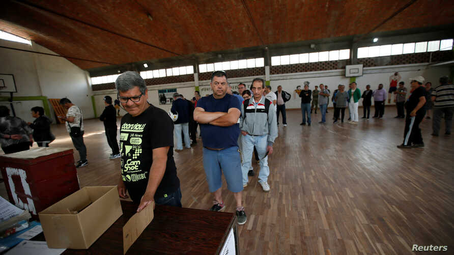 People stand in line to cast their votes at a polling station, in Montevideo, Uruguay, Oct. 27, 2019.