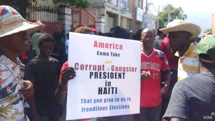 Protesters in Port-au-Prince, Haiti hold a poster demanding the US stop propping up the country's president during a protest, Friday, Oct. 4, 2019. (Photo: Matiado Vilme / VOA Creole)