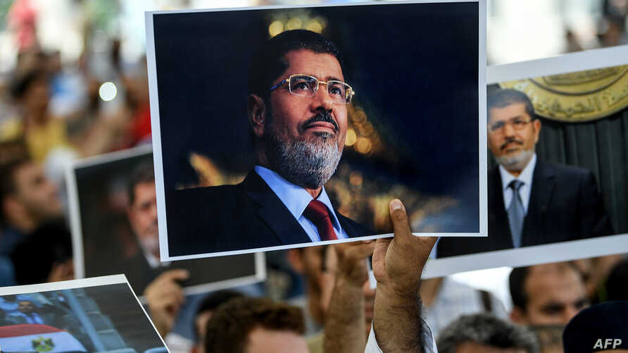 FILE - People hold pictures of Egyptian President Mohamed Morsi during a symbolic funeral ceremony at Fatih mosque in Istanbul, June 18, 2019.