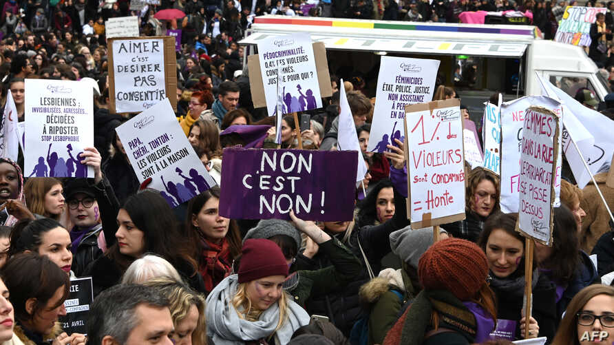 People hold placards against women's violence as they take part in a protest during the International day for elimination of…