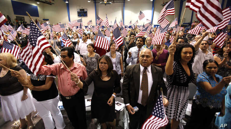People hold flags as they are sworn in as U.S. citizens during a naturalization ceremony on Tuesday, July 2, 2010 in Phoenix. …