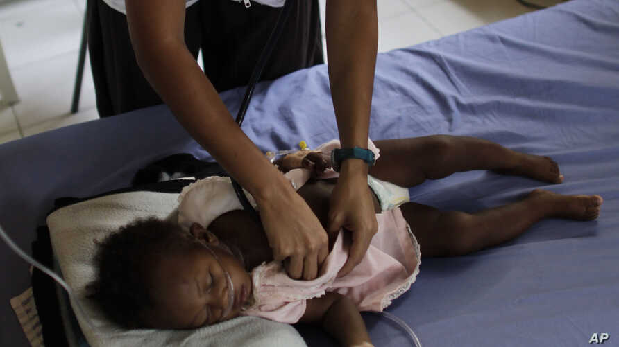 Maria Jose Caceres, a nurse for the relief organization Doctors Without Borders, or MSF, listens to the chest of a child with…