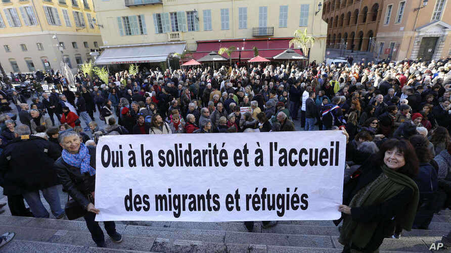 """A crowd supports Cedric Herrou, a French activist farmer who faces up to five years in prison as he goes on trial accused of helping African migrants cross the border from Italy, with a banner reading """"Yes to solidarity and Welcome migrants and refugees."""""""